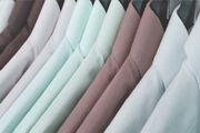 A rail of ironed shirts in different colours